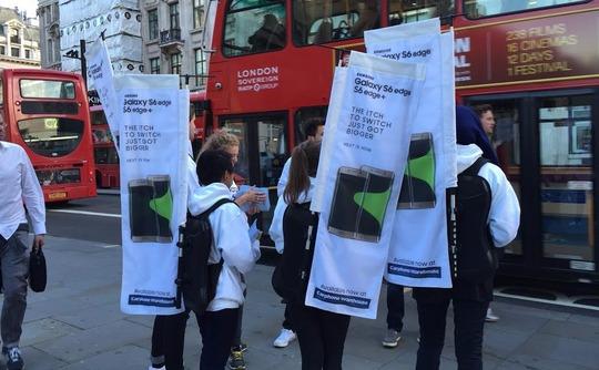 Cartelitos vendiendo el Samsung Galaxy S6 Edge en la cola de la Apple Store