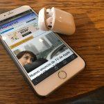 AirPods sobre un iPhone con iPhoneros abierta