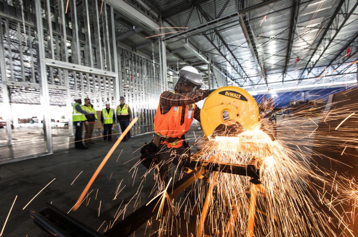 Foto de un señor cortando algo con la radial en una fábrica norteamericana