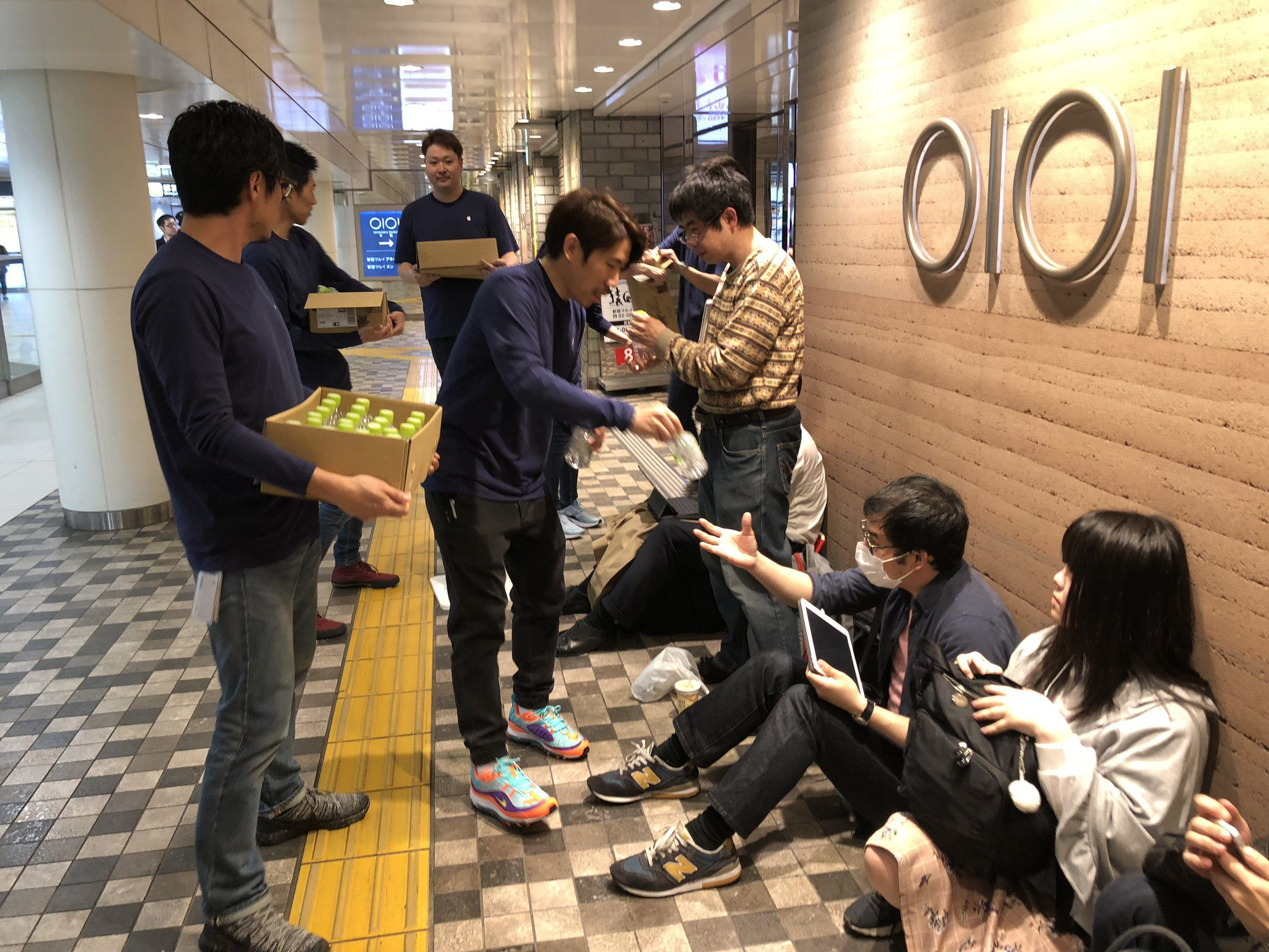 Repartiendo agua entre los que esperan a la inauguración de la nueva tienda de Apple en Shinjuku