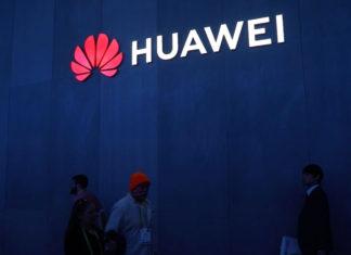 Personas caminando bajo el logo de Huawei